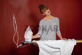 junge Frau bügelt ein Hemd
