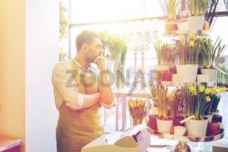 sad florist man or seller at flower shop counter