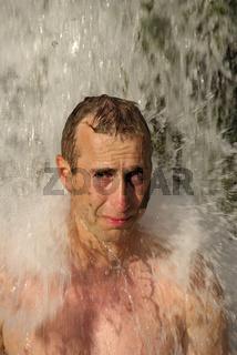 Mann unter einem Wasserfalll bei Roski Slap