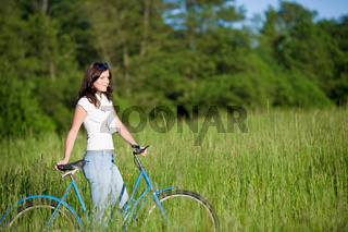 Woman with old-fashioned bike in summer meadow