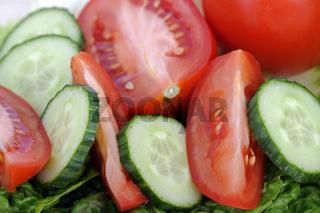 gruene Salatgurken, Blattsalat, Tomaten auf Schneidebrett
