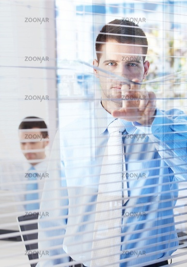 Handsome businessman peeping through blind