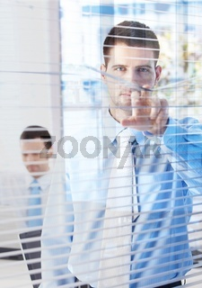 Handsome businessman peeping through blind
