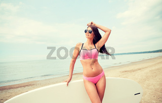 smiling young woman with surfboard on beach