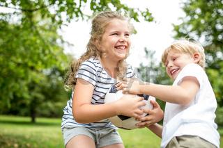 Kinder streiten um einen Ball