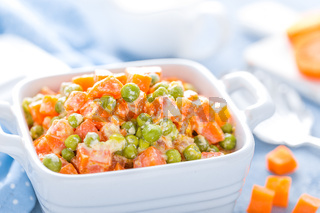 Green peas stewed with carrots in creamy milk white sauce, vegetable stew