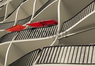 Fassade eines Wohnhauses mit zwei roten Sonnenschirmen