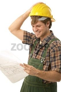 Confident handyman looking at floor plan