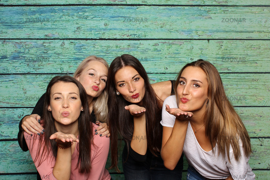 4 girl make blow kisses in a photo box
