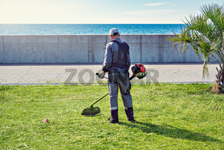 One man mows the grass.