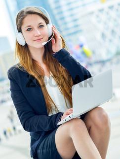 Blonde support operator in headset outdoor