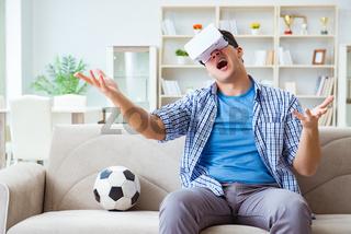Man wearing virtual reality VR glasses watching soccer football