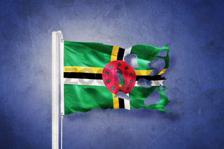 Torn flag of Dominica flying against grunge background