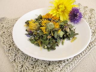 Kräuterteemischung mit Blüten auf einem kleinen Teller