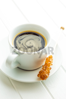 Brown amber sugar crystal on wooden stick and coffee cup.