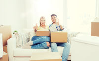 happy couple with boxes showing thumbs up at home