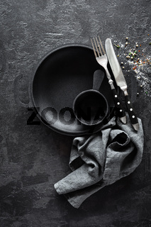 Empty cast-iron pan with cutlery on dark background for restaurant menu, top view