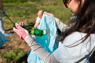 volunteer with trash bag and bottle cleaning area