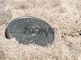 Swiss 5 Franc coin on sand