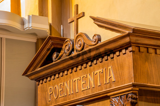 Latin word on a wooden confessional
