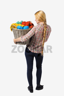 Back view of woman with  basket  dirty laundry. girl is engaged in washing.