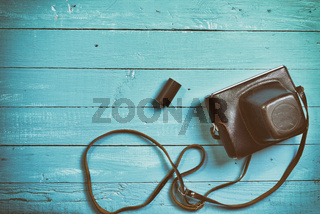 Vintage film camera in a leather case on a wooden camera