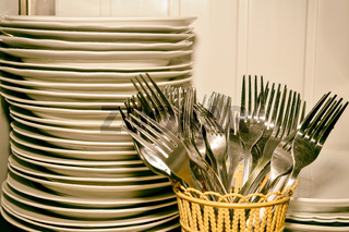 A stack of washed dishes and forks in the kitchen
