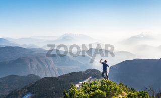Happy success winning man on mountain summit jumps for joy