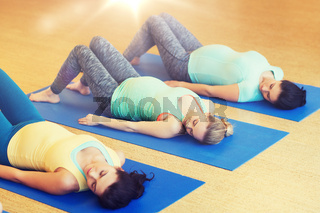 happy pregnant women exercising on mats in gym