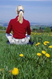 Blonde Frau mit rotem Pulli sitzt in der Wiese und geniesst den Frühling