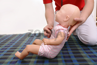 First aid instructor using infant dummy to demonstrate how to examine baby with stethoscope