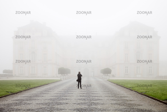Photographer in front of Schloss Augustusburg in the fog, Bruehl, North Rhine-Westphalia, Germany