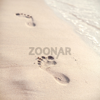 Soft focus and tone of footprints on the tropical beach sand with coast line. Journey  and leisure concept.