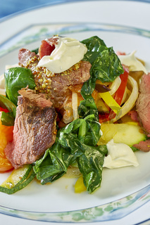 meat salad with green tomatoes on the plate blue background lot of food recipes