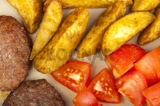 Beef burgers with potato wedges and fresh tomato's
