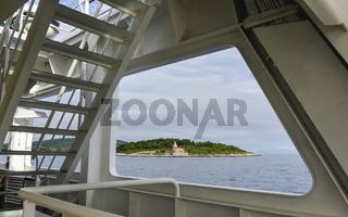 Fährschiff passiert eine Insel mit Kapelle