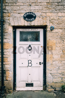 Limestone cottage entrance. Painted wooden  door.