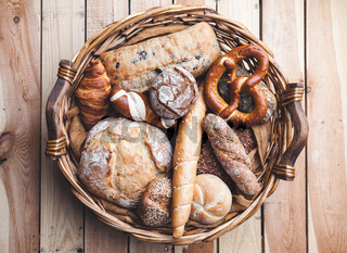 A basket full of delicious freshly baked bread on wooden background