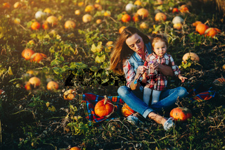 mother and daughter on a field with pumpkins