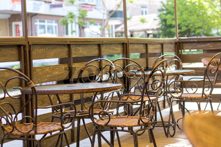 Cosy terrace of the summer cafe with wicker tables and chairs