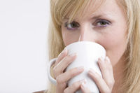 Portrait of beautiful girl with white tea cup at h