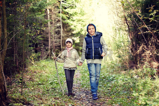 two happy kids walking along forest path
