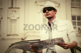 Young fashion man with a road map next to vintage car
