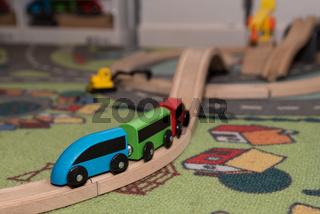 bunte Spielzeugeisenbahn aus Holz mit Schienen und Spielzeugteppich