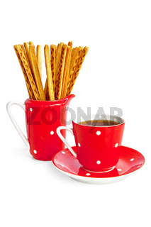 Bread sticks and coffee in the red utensil
