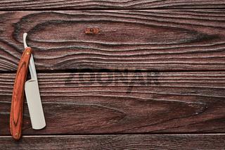 Vintage barber shop straight razor tool on wooden background