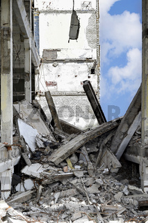 Chunks of concrete and metal on a background of a wall of the destroyed building and blue sky Chunks of concrete and metal on a background of a wall of the destroyed building and blue sky