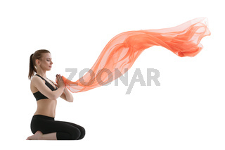 Yuong girl doing yoga posing with red cloth