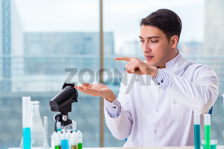 Young chemist student working in lab on chemicals