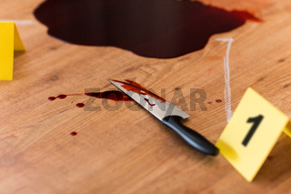 knife in blood and chalk outline at crime scene